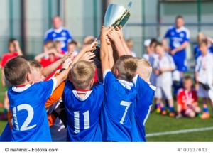 Young Soccer Players Holding Trophy. Boys Celebrating Soccer Football Championship